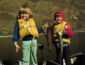 Two girls smiling with fish in hands